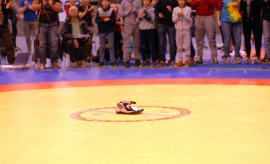 SKOENE PÅ MATTEN: Etter matchen ble Thomas sittende på matta, tok av seg skoene og lot de bli stående igjen mens han forlot matta og brytinga som utøver til øredøvende applaus. Dette er tradisjon for store brytere som legger opp.