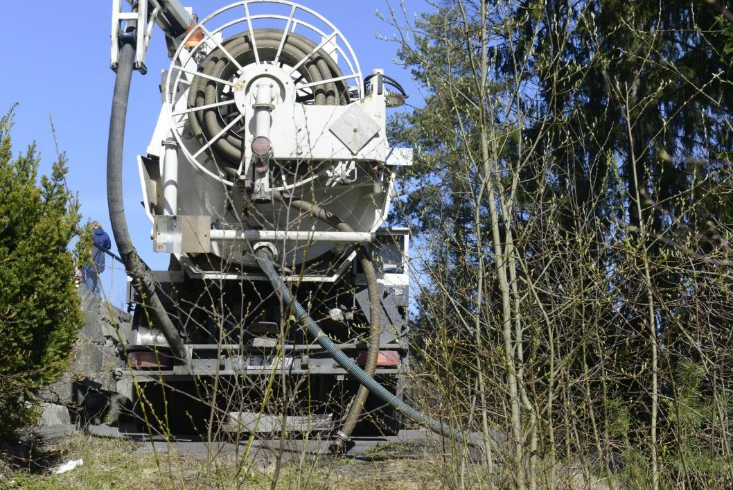 OPPSUGING: Store slanger fra en lastebil går ned til Myrvollbekken og suger opp oljen.