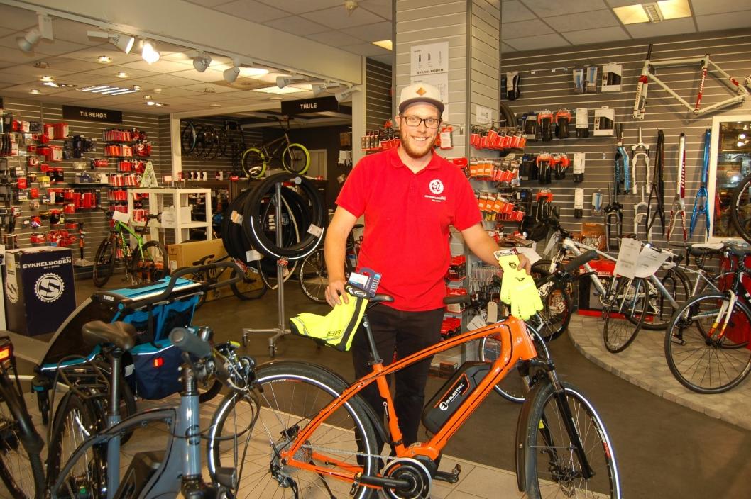 GJØR DEG SYNLIG: Christian Lindelund ved Sykkelboden viser fram noe av det du kan kjøpe for å gjøre deg mer synlig: reflekser eller en oransje sykkel!