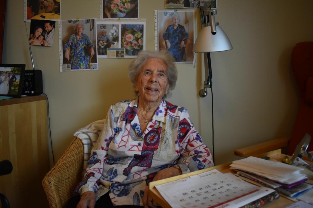 ET GODT LIV: – Jeg har hatt et godt liv, og har ingenting å klandre samfunnet for, sier den positive 104-åringen. Her sitter hun i leiligheten sin på Greverud sykehjem, hvor hun trives svært godt. På bordet har hun et glass rødvin og en boks sjokoladehjerter. – Sønnen min tar med seg rødvin hver gang han kommer på besøk, sier hun og smiler.