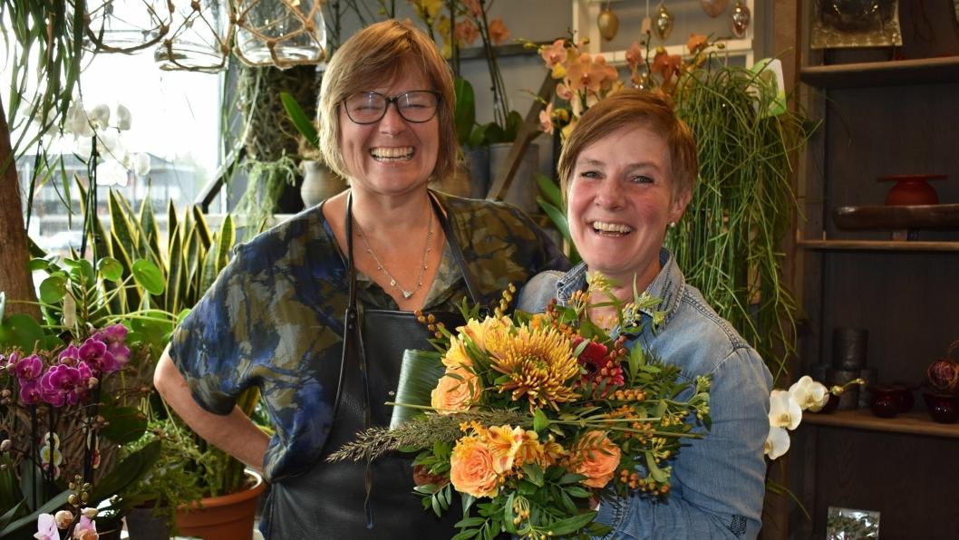 FRUER MED FART I: Åse Hoff og Elin Rustad driver Fruene Fryd og Gaven AS, og kan det meste som er å kunne om blomster. Her stråler energien, og latteren sitter løst! Rustad holder en nylaget bukett i høstlige farger.
