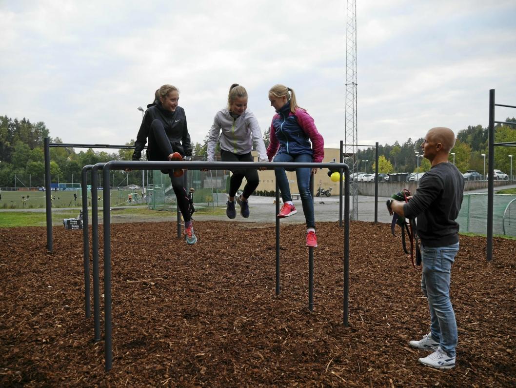 KOSTE SEG: Marie Røed, Synne Borge og Kine Rye Holmboe fikk øvelser demonstrert av Lasse Tufte under åpningen. Jentene koste seg åpenbart i den nye parken.