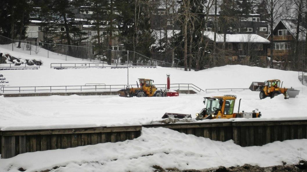 HER JOBBES DET: Kommunens arbeidere jobber hardt for å få snøen fjernet og banen klar til seriestart.