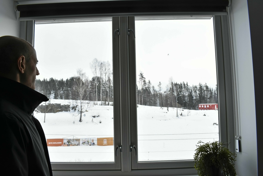 SPEIDER: Prosjektsjef Moe titter ut på det som skal bli Myrvoll Stasjon. Mellom vinduet og trærne går toglinjene.