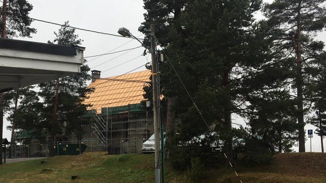 KOLBOTN KIRKE: Ligger der bak trærne, og en av leserne våre har knipset dette bildet av det nye kirketaket.