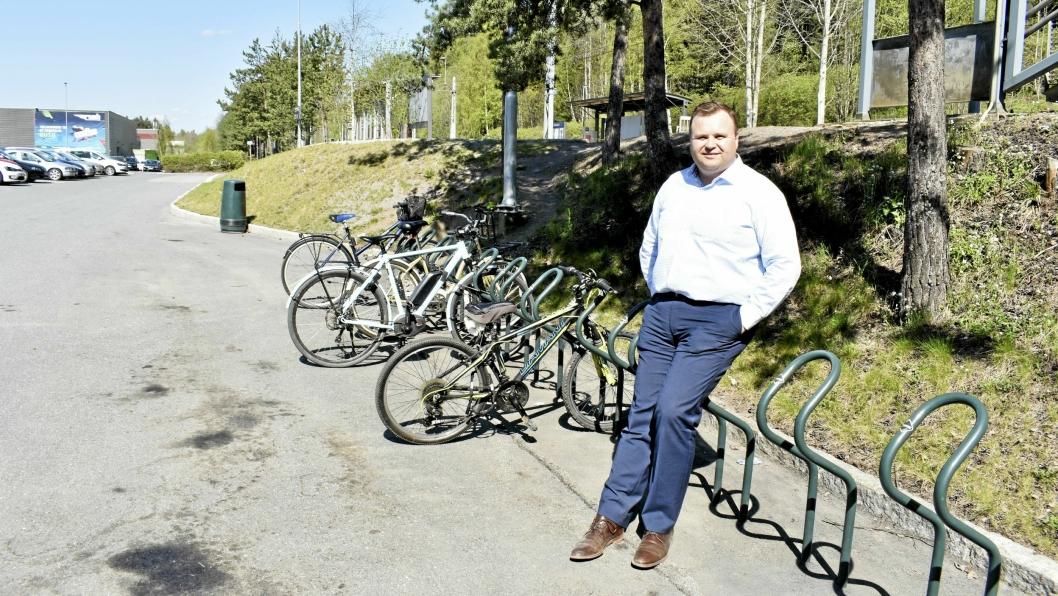RAMMETILLATELSE I BOKS: – Vi ønsker sykkelhotellet etablert så raskt som mulig, men kan ikke gi noe nøyaktig svar før økonomien er endelig avklart, sier ordfører Thomas Sjøvold. Kommunen har fått rammetillatelse, men prosjektet ble mer kostbart enn først antatt. Nøyaktig hvor det blir, er heller ikke avklart, og her står Sjøvold ved Rosenholm stasjon. På andre siden av Rosenholmveien leies den kommunale tomten nå ut til Unibuss.
