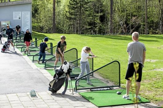 AKTIVT MILJØ: Hektisk aktivitet på rangen allerede før åpning. Her slår Tine Daae (14) sine aller første golfslag, mens mens far Trygve Daae følger med.