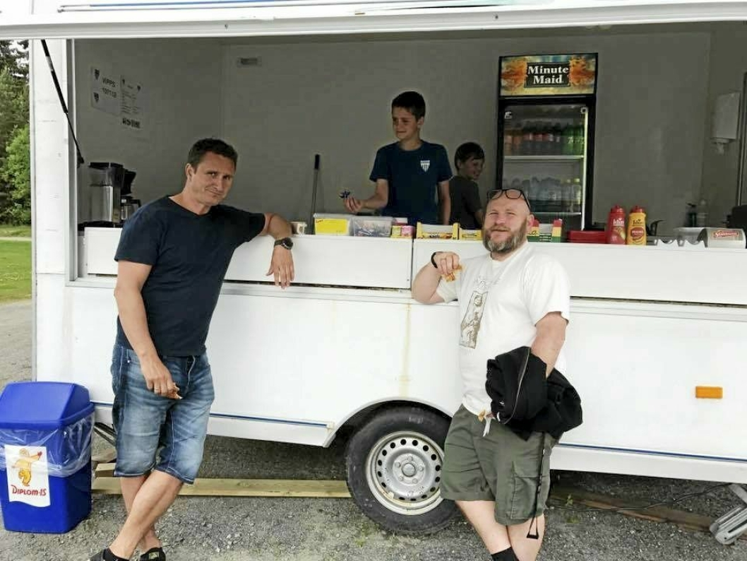 EN PØLSE, TAKK! Banekiosk er sosiale saker. Her har herrene Erlend Z. Gundersen og Espen Mossin overlatt serveringen til hver sin junior - Jakob (foran) og Tobias. Bildet er tatt i fjor.