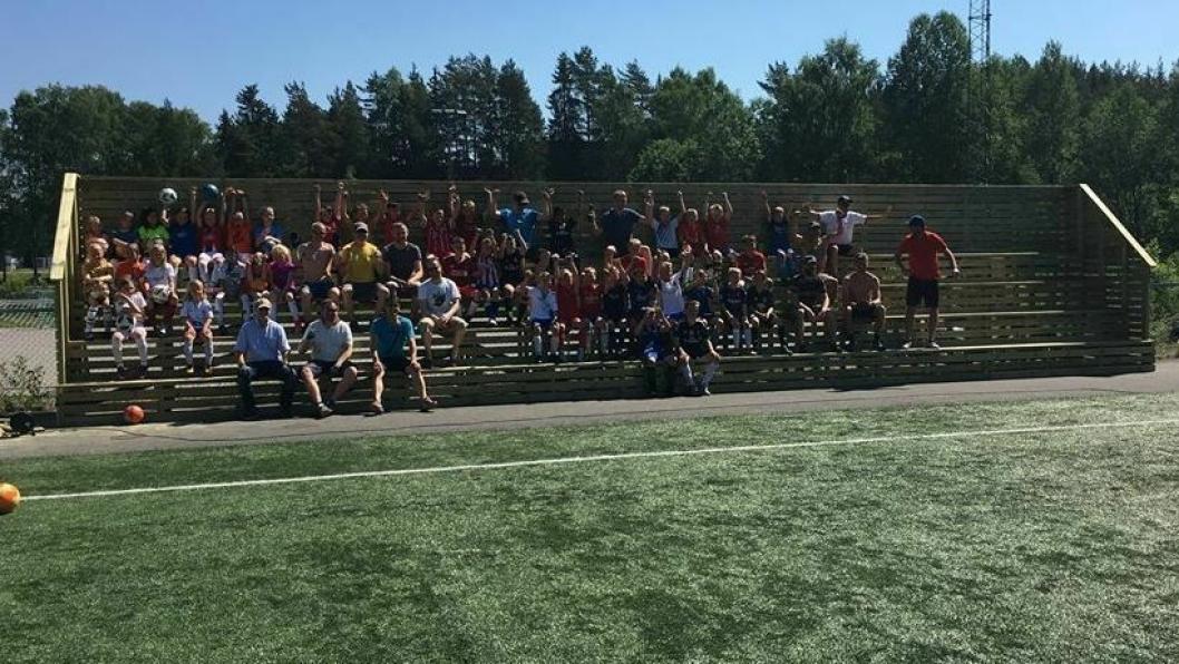 INNVIET: Glade fotballbarn og dugnadsgjengen prøvesitter den nye tribunen. Bildet, som ble tatt søndag klokken 12.00, viser bare halvparten av tribunen.