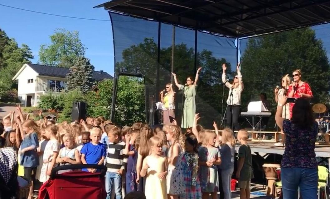 I SKYGGEN AV ET PALMETRE: Lærerne stod for avslutningssangen, og fikk barn og foreldre med seg i klappingen.