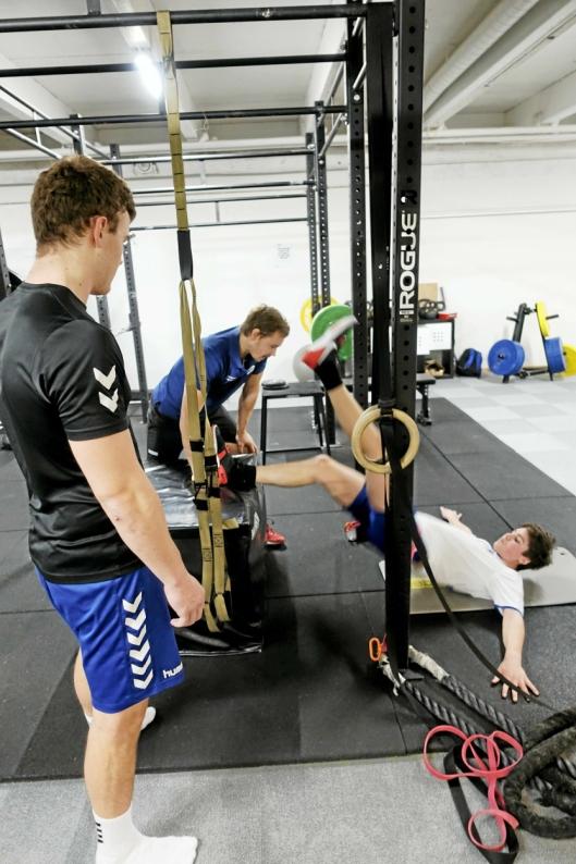 PÅ GØLVET: Jonas Dahl Michelsen (liggende) trener kjernemuskulaturen under oppsyn av fysisk trener Jørgen Aasen (lengst unna) på Atlet.