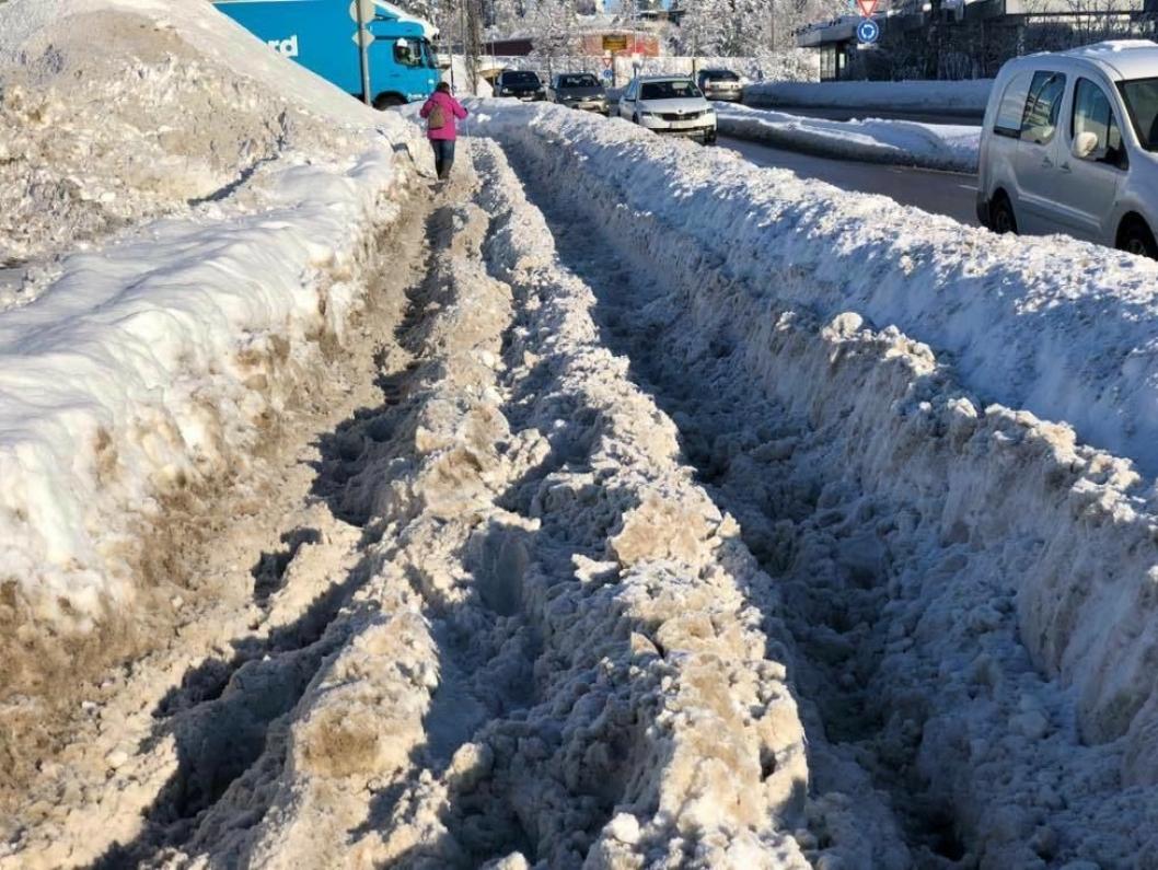 """DETTE ER SKI SENTRUM: Dette bildet, som ble tatt av Svein Arne Grindstad i Ski sentrum 8. februar i år, beskriver situasjonen mer enn tusen ord. """"Gangveien utenfor XXL i går (8. februar) før regnet kom. Totalt ufremkommelig og slik har den vært i flere dager. Og slik var det i fjor også. Svært kritikkverdig"""", skrev Grindstad på Facebook-siden Hva skjer i Ski? 9. februar. Riks- og fylkesveiene eies av Statens vegvesen (SVV), så det er SVV og ikke Ski kommune som har ansvar for vintervedlikehold av denne veien, men dette gjør ikke livet lettere for syklistene."""