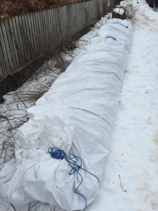 BLE DEKKET INN: Kreosot-stolpene ble lagt på presenning og pakket godt inn torsdag 14. mars. Bildet ble sendt inn til kommunen av leverandøren, Viken Energimontasje AS.