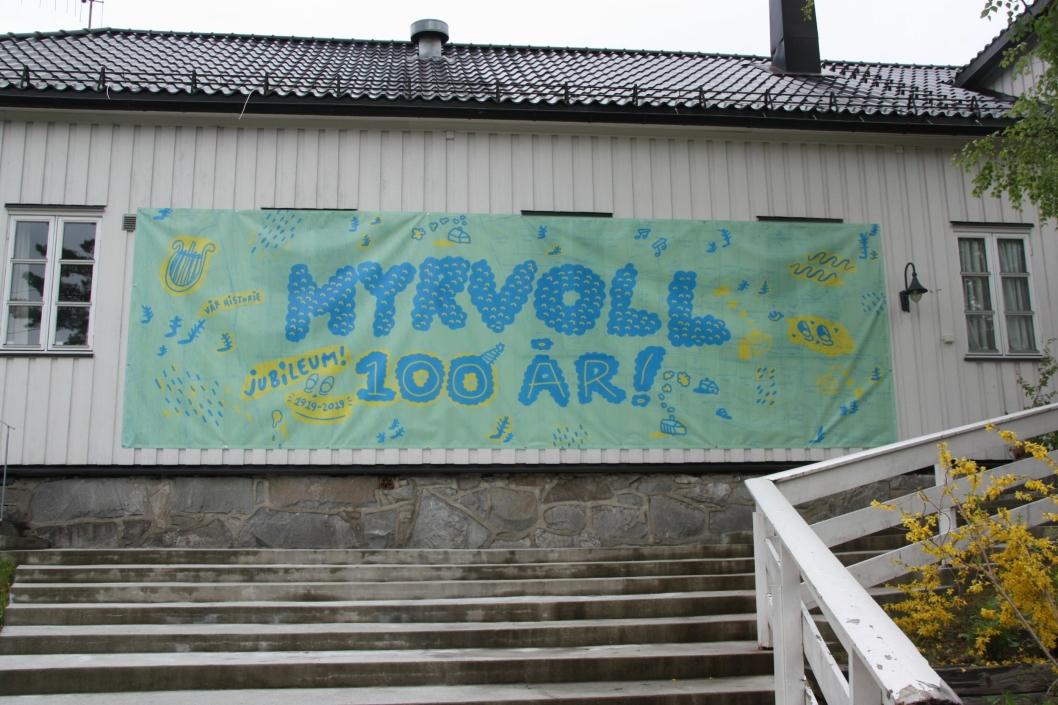 JUBILEUMSBANNER: Lørdag 18. mai begynte Myrvoll Vel å henge opp jubileumsbannere. På bildet ser du et banner på 2,5x8 meter som dekker frontveggen på Fjelltun.