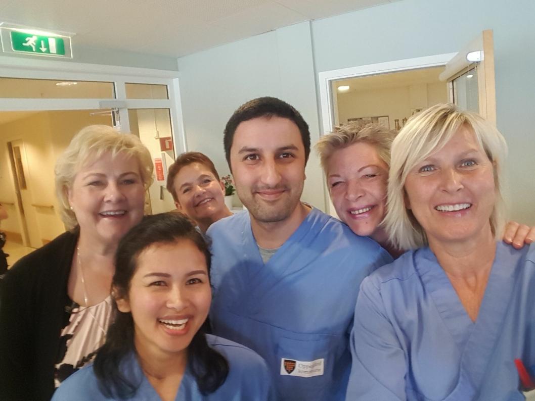 SELFIE: De ansatte ved Greverud sykehjem hadde god grunn til å smile sammen med statsministeren. Foran til venstre Wibunrat Sanan, i midten Josef Khan, bak til høyre Hilde Restoft og helt bak Hege Botner. Til høyre holder Margit Djønne Andersen selfiestanga.