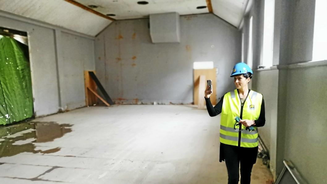 SIKRER MINNER: Rektor Kristin Hovde Høidal filmer slik det ser ut i den gamle gymsalen etter at den er blitt strippet ned.
