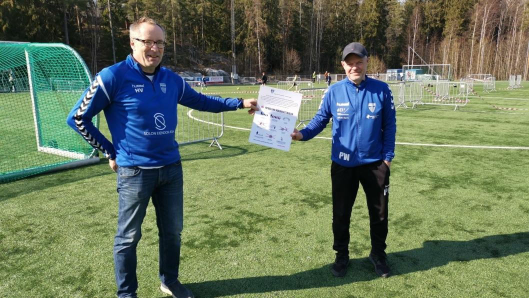 NYE REGLER: Harald Vaadal (t.v.) og Pål Wirak hengte mandag opp nye oppslag med retningslinjer for fotballtrening.