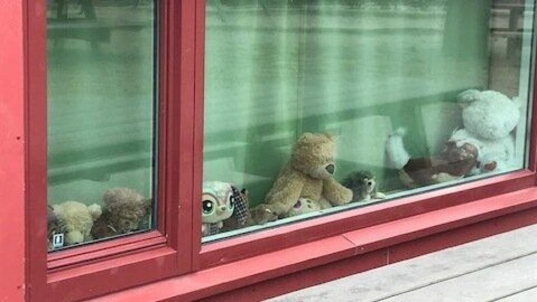 VENTER I VINDUET: Bamser og dukker plassert i vinduene til barnehagen.