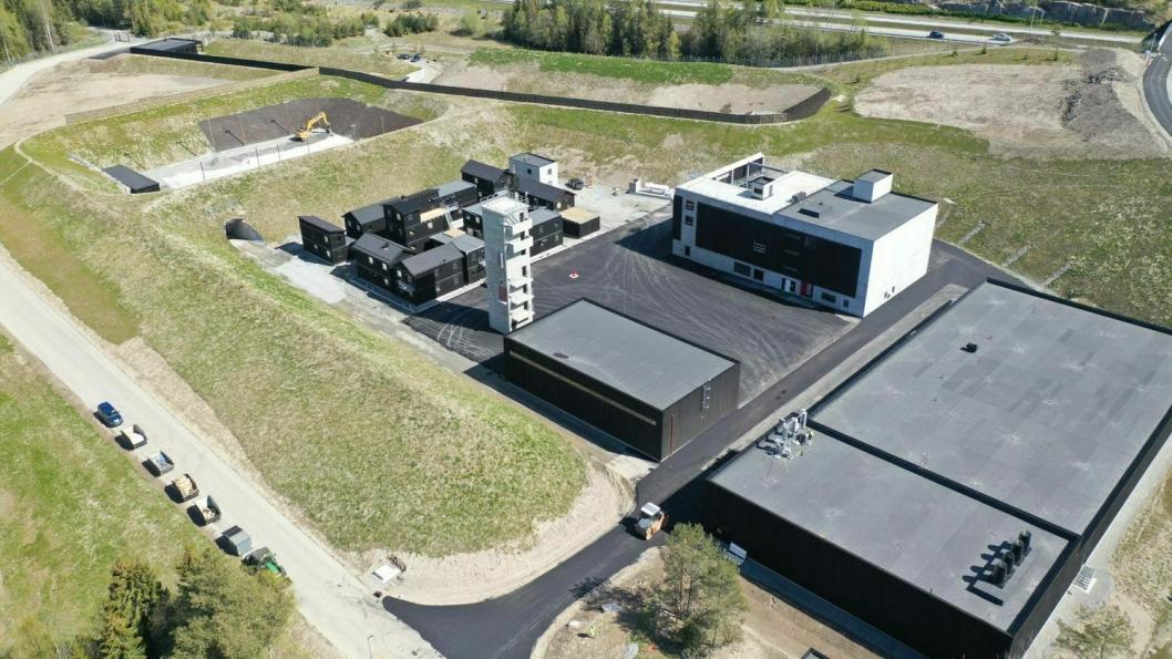 Bildet viser treningsområdet med innendørs skytebane, skytehus og klatretårn i forgrunnen. Du kan også se SIBO-landsby (Strid I Bebygd Område) og utendørs skytebaner i bakgrunnen.