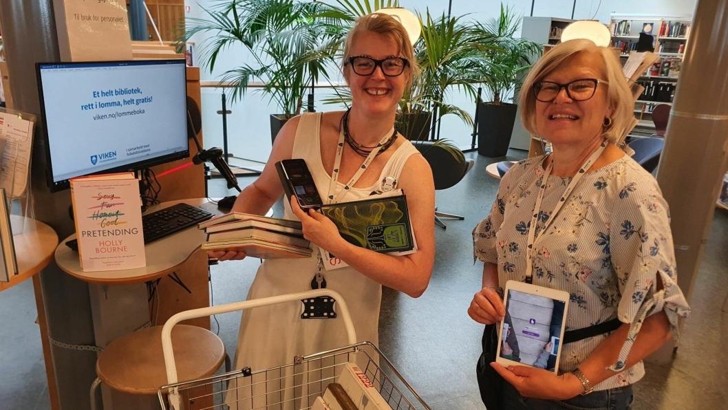 ENKELT OG GRATIS: Bibliotekarene Kristine Mesgrahl og Guri Grimstad ved Nordre Follo bibliotek, avdeling Kolben, anbefaler alle å teste bibliotekets digitale tjenester i sommer. – «Lommeboka» er et helt bibliotek i lommen, helt gratis! sier de to bibliotekarene.