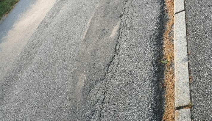 SLITT ASFALTDEKKE: Holbergs vei får ikke ny asfalt i år heller. Det er tydelig at denne veien har store behov for ny asfalt, men prosjektet har stått på vent i flere år. Foto: Yana Stubberudlien