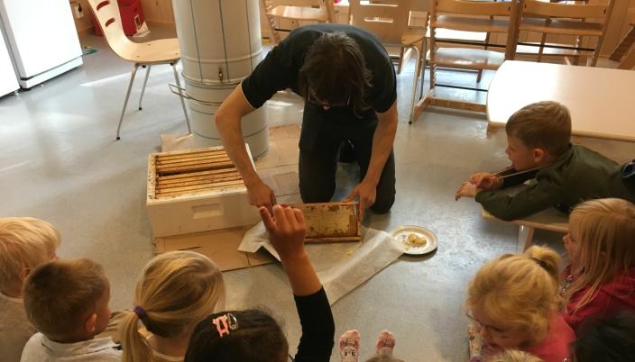 FJERNER VOKS FRA RAMMEN: På bildet ser du birøkter Mikkel Dagestad som fjerner voks før rammen settes i trommelen for slynging. Foto: Hareveien barnehage