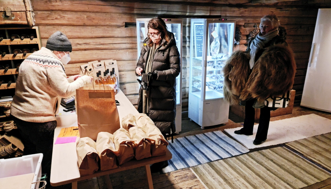 SALG PÅ STABBURET: Kundene står pent på geledd når Hilde Aukrust ekspederer i gårdsbutikken på stabburet. På disken ligger både pakker med pinnekjøtt og eplemost av epler fra gården.