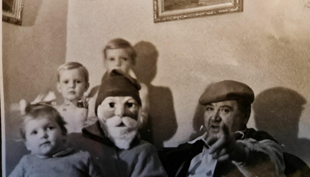 JUL PÅ «ÅSEN»: Dette bildet er fra cirka 1950. Artikkelforfatter Espen sitter til venstre for nissen, og til høyre hans bror Pål. Foran til venstre sitter guttenes kusine Kjersti på nissens fang. Hennes tvillingsøster Lisbet nektet å nærme seg nissen. Bestefar, driftsbestyrer Karl Aasen på Oppegård E-verk, sitter med sin trofaste røde alpelue til høyre for nissen.
