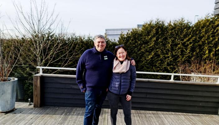 NÆRMESTE NABO: Maia og Henrik Holthe smiler tross at bygningen bak hekken kan bli vesentlig høyere dersom kommunedirektørens innstilling vedtas av politikerne.