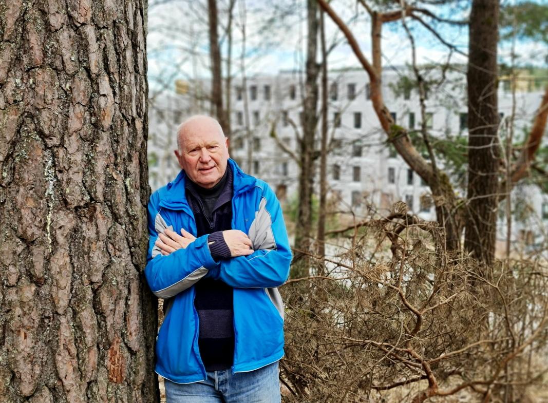 VIL BEVARE: Steinar Karlsrud og Oppegård historielag kjemper for bevare Kollen i Kolbotn sentrum. Her står Karlsrud midt i den lille skogen som er igjen i Kolbotn sentrum. I bakgrunnen er veien kort til de nye blokkene i Storebukta.