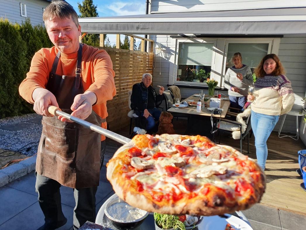 """SMAKEN AV ITALIA: """"Prego! Vær så god!"""" sier Espen Kronlund (50). Det er han som har ansvar for vedfyring og pizzasteking, mens kona Lene Kristine (47) sørger for deigen. På bildet kan du også se svigerforeldrene Terje og Synnøve som koser seg med nystekt pizza. Foto: Yana Stubberudlien"""