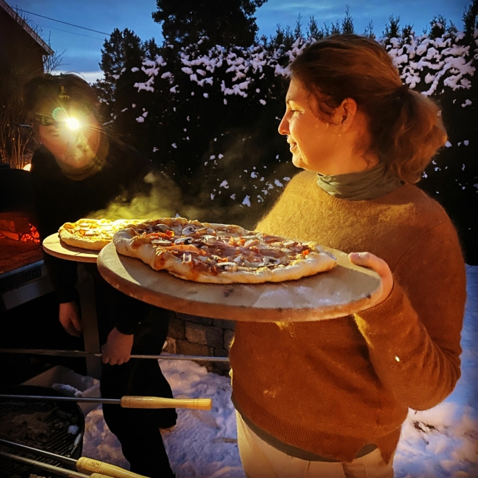 VINTERPIZZA: På bildet kan du se Espen, utstyrt med lommelykt, klar for å sette Lenes pizza inn i ovnen på en kald vinterkveld. Foto: Privat