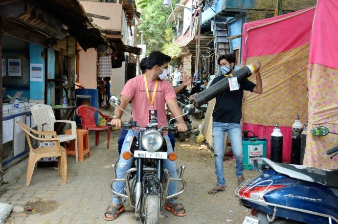 DELER UT OKSYGENFLASKER: Flere har engasjert seg i utdeling av oksygenflaskene i Mumbai. Foto: Terhi Width