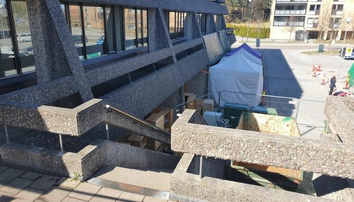 TESTER FOR COVID-19: Tidligere i år har det blitt opprettet en midlertidig koronateststasjon i nordvestre del av byggets underetasje. Ved siden av teltene til koronastasjonen kan du se kontainerne i forbindelse med ombyggingen av rådhuset. Foto: Yana Stubberudlien