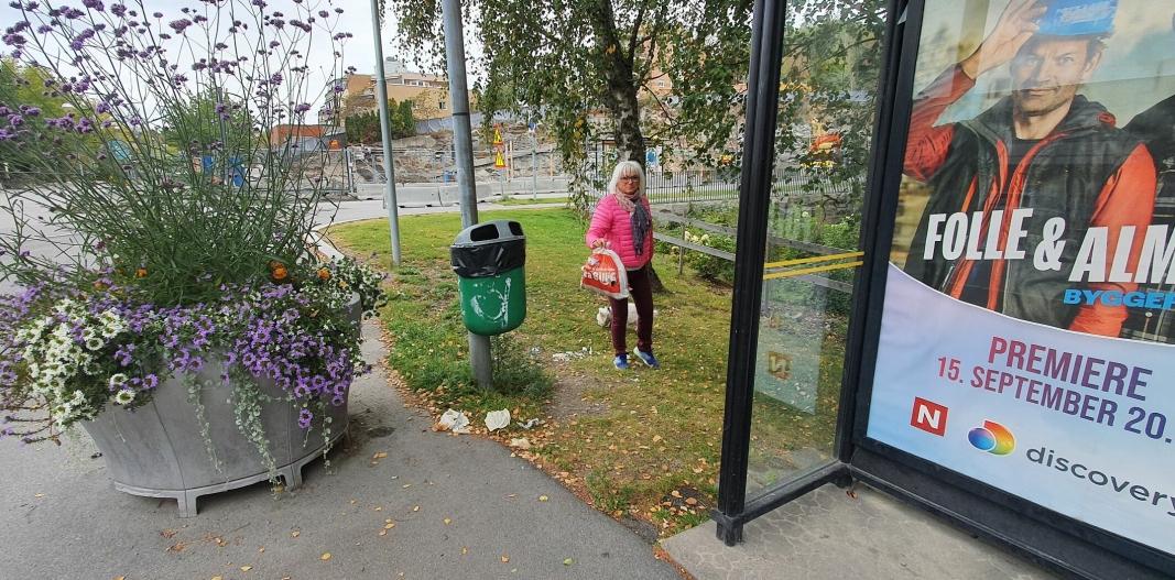 BLOMSTER VS. SØPPEL: Foran den overfylte søppeldunken har kommunen satt opp en stor blomsterurne med flotte blomster, men det er søppelet som sjenerer Berit Kaarbø og flere andre innbyggere vi har snakket med. Foto: Yana Stubberudlien