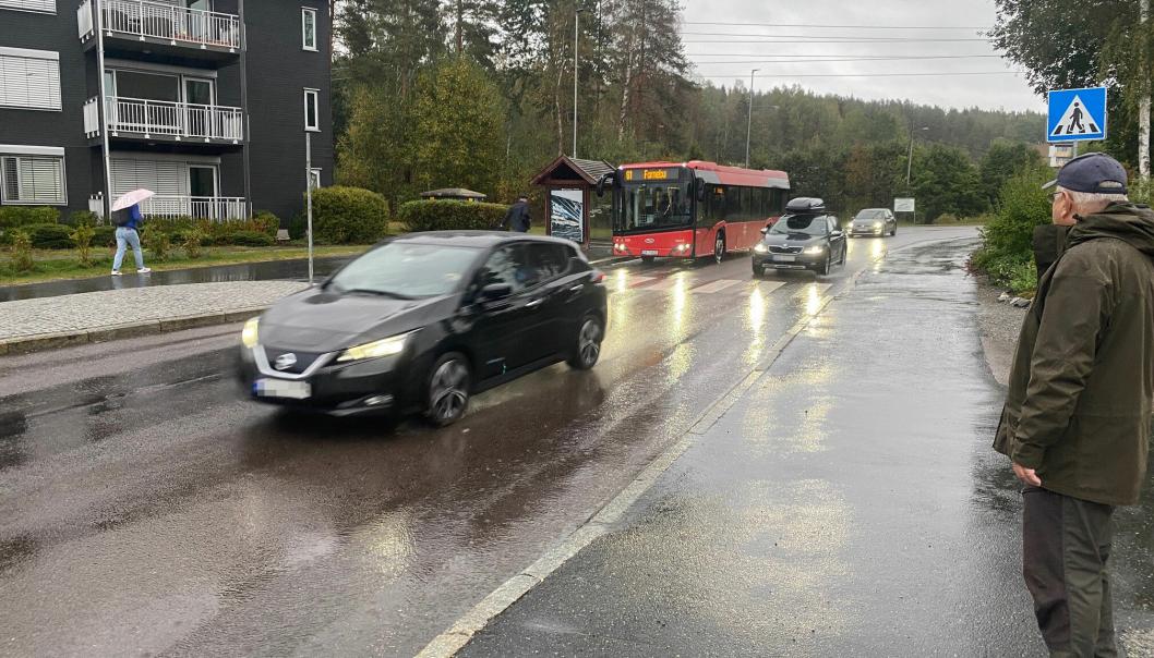 BEKYMRET: Rolf Arnesen ser bekymret på at bilene suser forbi bussen på holdeplassen.